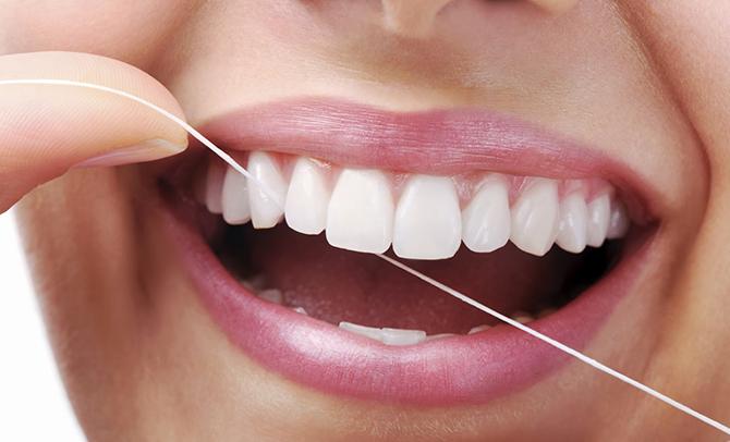 O fio dental é fundamental, pois ele chega onde a escova não consegue.
