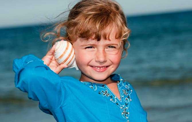 Ouvir o som do mar na concha é uma das felicidades da criançada